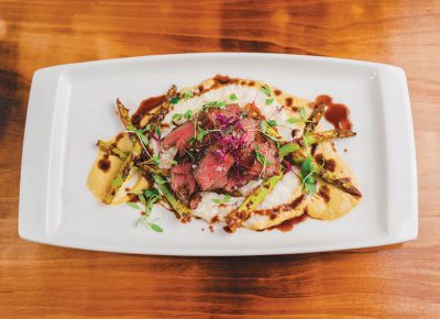 The Betel Smoked Beef rests on a bed of asparagus, reamy grits and Bordelaise.