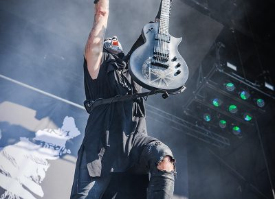 Guitarist of opening band Behemoth rocks with his arms raised to the sky.