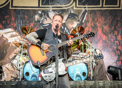 Wielding two guitars, Volbeat lead singer Michael Poulsen sings as he picks out an acoustic melody.