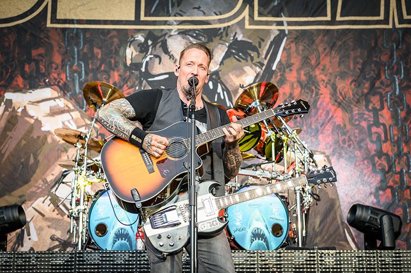 Wielding two guitars, Volbeat lead singer Michael Poulsen sings as he picks out an acoustic melody.