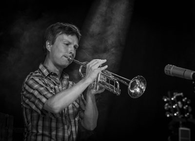 A ray of light falls on Dave Jorgensen, trumpeter for Blind Pilot, as he blasts on his horn!