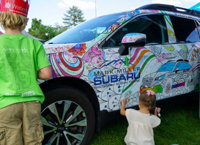 Children doing some art work on the Subaru.