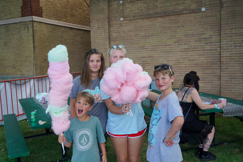 Kids posing with their collection of cotton candy in the Harmons VIP Area.