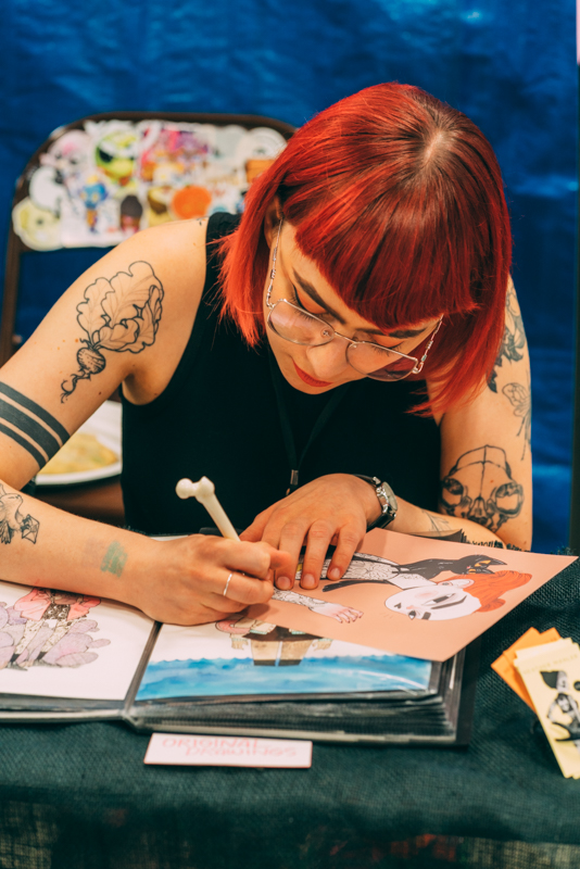 Heather Mahler signs a signature print for a local collector.