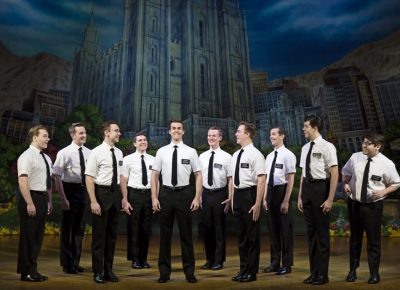 A shining group of missionaries on stage during The Book of Mormon at The Eccles Theater.