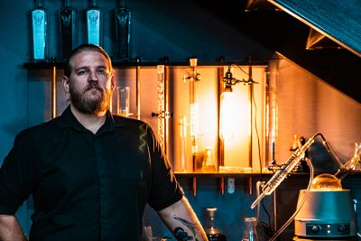 Holystone Distilling Head Distiller Ethan Miller (Top) has plans for many firsts for the speakeasy-feeling distillery, alongside Co-owners Mike DeShazo and Barbie Busch DeShazo (not pictured).