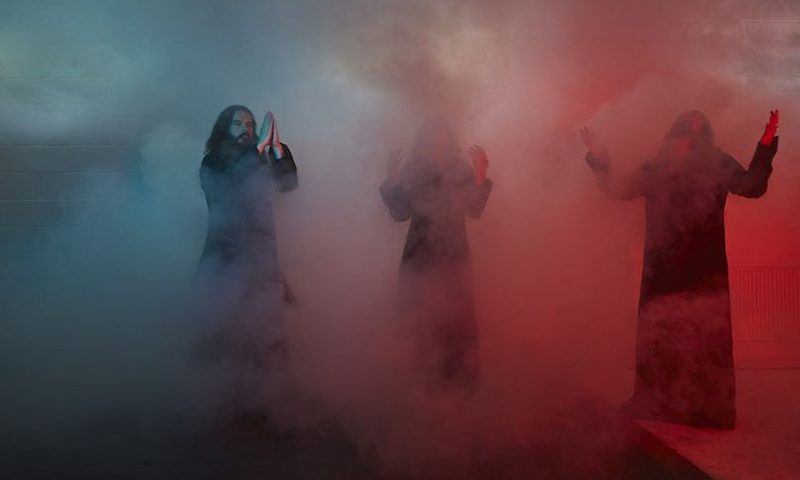 Sunn O))) bathed in blue and pink lights.