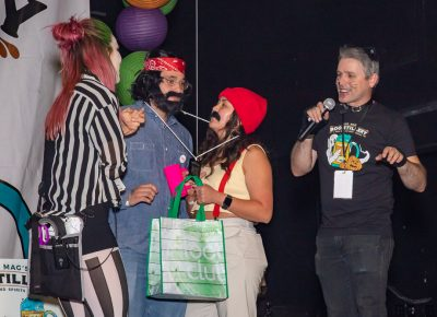 (L–R) Drea Bedke awards Matt Arellano as Cheech and Lashena Stevens as Chong third place in the Boo!stillery costume contest as John Ford narrates the action.