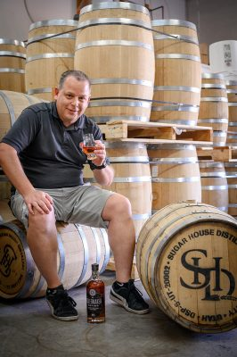 Head Distiller James Fowler sits with some of Sugar House Distillery's barrels.
