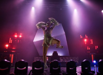 Dancing in front of a visually captivating scene, the electropop artist Charli XCX exudes energy throughout her performance.