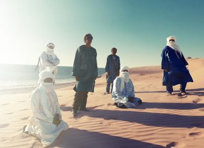 Members of Tinariwen cast shadows upon the desert.