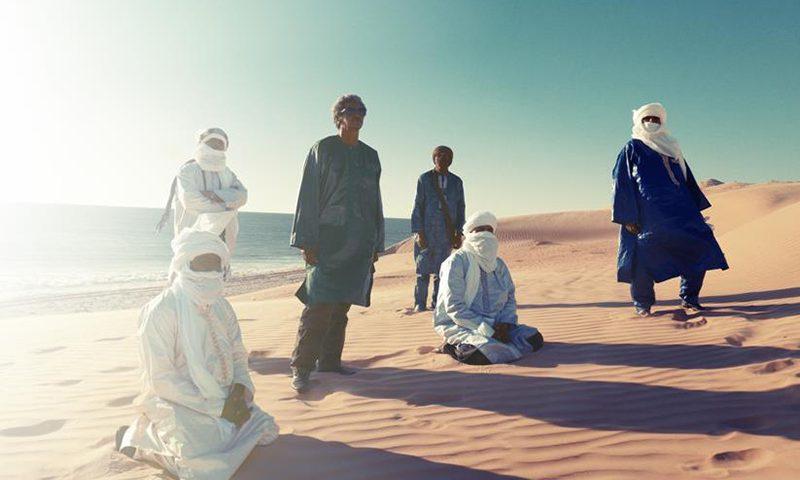Members of Tinariwen cast shadows upon the desert.