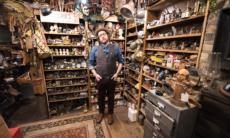 Jake Buntjer smiles from within his densely-stocked studio.
