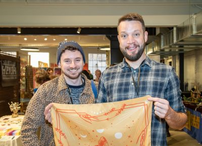 (L–R) Matt Kastellec and Nick Hoffman volunteered to help with load-out after the market closed. In the meantime, Hoffman bought a bandana that will tickle the Christmas bone of a colleague who's obsessed with lunar eclipses.