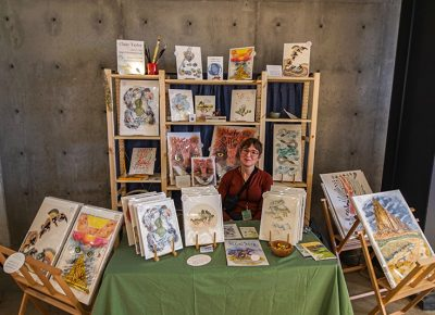 Claire Taylor at her vendor booth selling some of her amazing art.