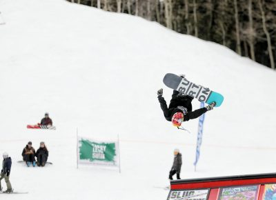Snowboarder in the air during a flip off the jump at the SLUG 20th Anniversary Meltdown Games at Brighton Resort.