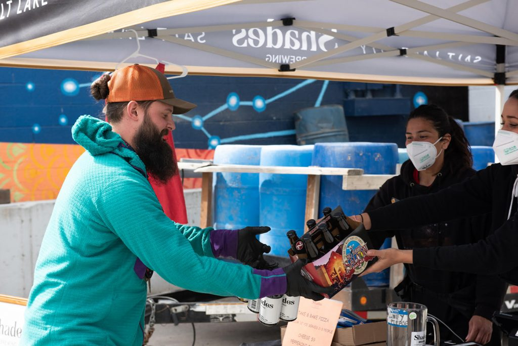 """An excited beer drinker receives service from the Shades retail team. """"Our customers' support has made it possible to keep all our employees employed,"""" says Co-Owner Alexandra Ortiz de Fargher."""