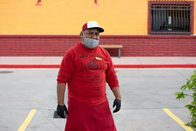 Red Iguana employee Israel Jimenez decked out in PPE gear to help with to-go food operations. He is one of the restaurant's 200-plus employees whose jobs are endangered by the pandemic.