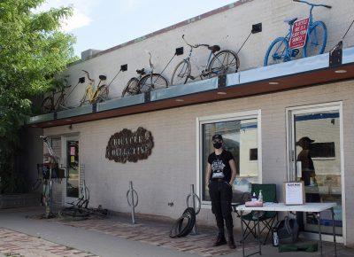 A SLUG Cat volunteer represents SLUG in front of the SLC Bicycle Collective.