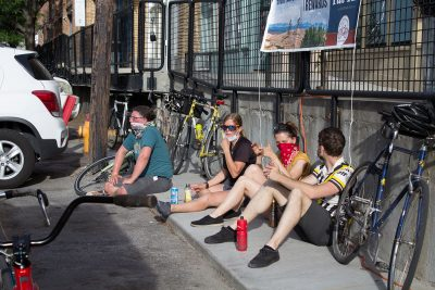 Some of the top SLUG Cat finishers engage in bike talk while perched on the ground.