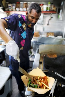 Abudujannah Soud plates a finished dish from his Kafé Mamai food truck.
