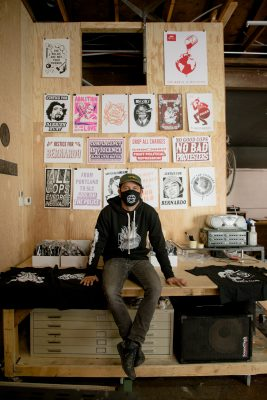 Nick Jones sits in front of the radical designs that are a hallmark of Surmise Clothing Company.