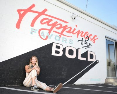 Alli VanKleeck of Hot Slice Design poses next to one of her murals.