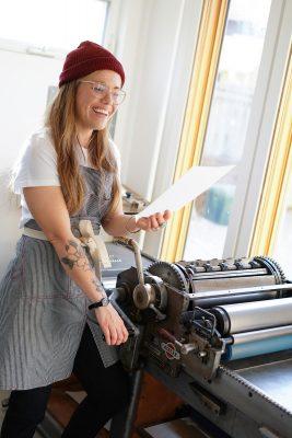 Allison Bitzer at work on one of Half Pint's vintage printing presses.
