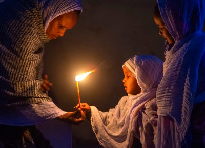 A mother hands a candle to her young daughter, during an early morning candle-light walk in Axum, Ethiopia, on Thursday, March 12, 2020.
