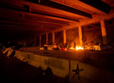 A few of the remaining campers warm themselves by the fire under the freeway over pass, on the last night of Camp Last Hope, on Wednesday, Feb. 3, 2021.