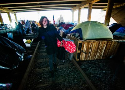 A woman named Ash heads to her tent after making a salad in the kitchen area at Camp Last Hope, on Tuesday, Jan. 5, 2021. As a vegetarian, she was delighted to see that fresh lettuce had been donated today.