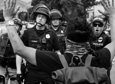 Salt Lake City Police warn a protester not to take a step further, as crowds were pushed back block after block, during a protest of the killing of George Floyd on Saturday, May 30, 2020.