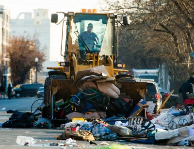 A front-end loader scoops up tents, sleeping bags, blankets and bikes, as the health department sweeps the area, loading everything into dump trucks on Wednesday, Dec. 9, 2020.