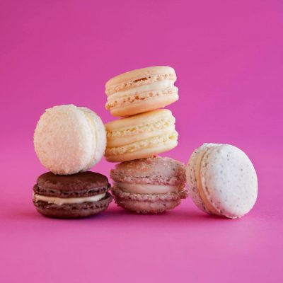 A bright pink background with delicious looking macaroons stacked on top of each other, perfectly balanced.