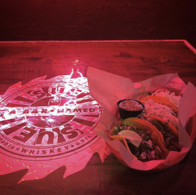 A classic burger dish is illuminated in the neon glow of the bar light, highlighting the Sue logo on the table