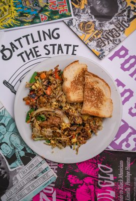 The Garbage Hash offers fried potatoes, curry seasoned tofu scramble, spicy and crumbly sausage and onions on a bed of greens with salty toast.