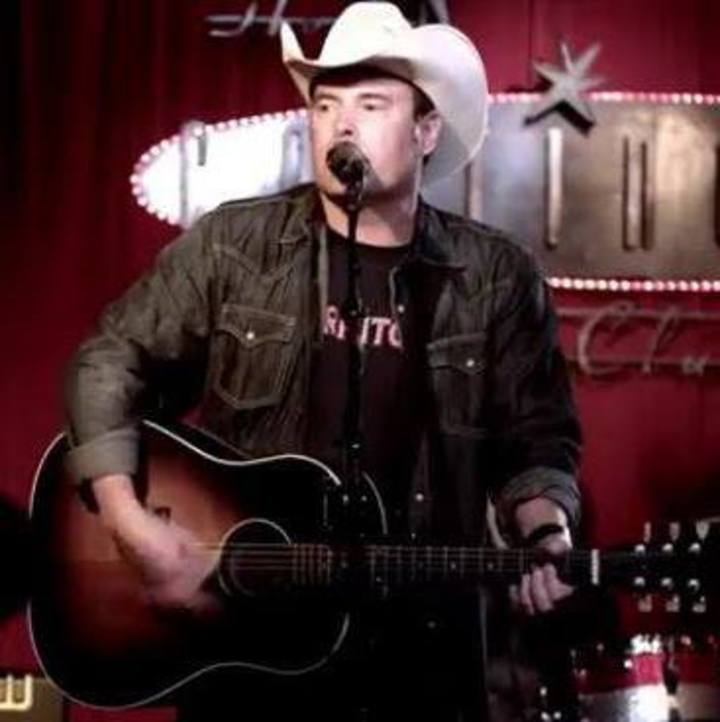 A cowboy playing guitar.