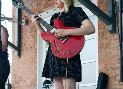 Audrey Lockie playing guitar in The Mercy Seat.