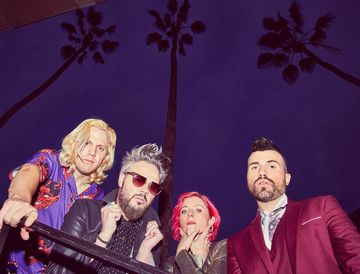 A purple hued photo of the members of Neon Trees in their finest attire with palm trees in the background.