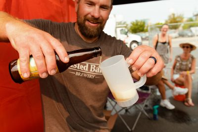 Toasted Barrell Brewery carefully pouring a sample of their signature sour beers.