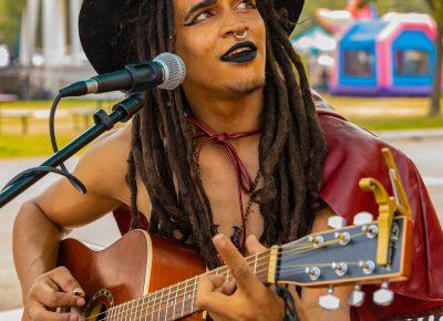 Muscian Zaza providing music for the Busking Bus Theatre Company.