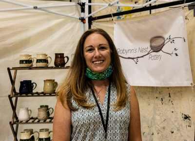 Robynn's Nest Pottery enjoying the afternoon at her booth in the Dreamers building.