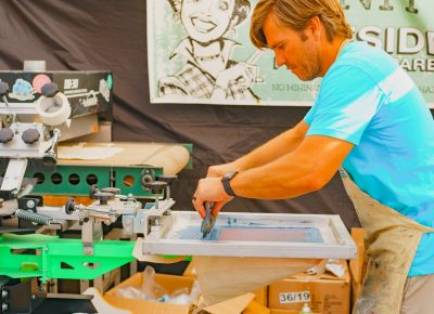 A local artisan makes some custom screen printing on site for our CLC guests.