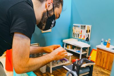 A CLC guest puts his hands to the test at Trishelle Jeffery's miniature art display.
