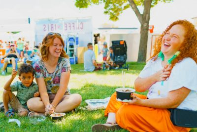 A couple of friends enjoy some shade and Cupbop while listening to the performers on stage.