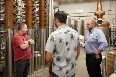 Distillery Owner James Fowler talking business with patrons, including Clinton Fowler of Pago.