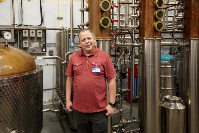 Owner James Fowler posing in front of some of the distillery equipment.