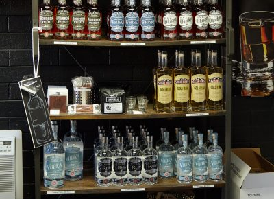 A shelf display of the available liquors and some merch items for sale.