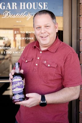 Owner and Master Distiller James Fowler poses in front of the distillery doors with a bottle of the new Barrel Master #2 Rye Whiskey.